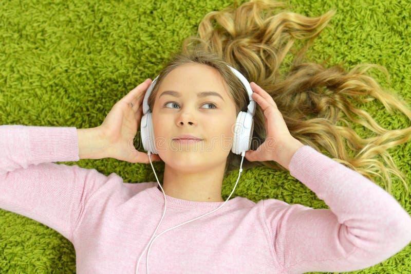 Девушка лежит на поле и слушает к музыке стоковое фото