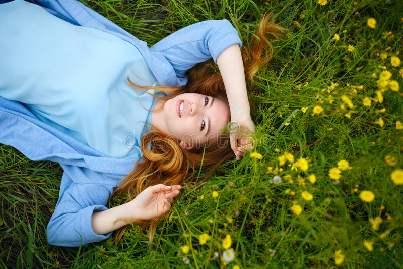 Девушка лежит на лужке стоковая фотография