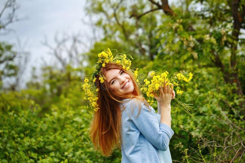 Девушка держа букет полевых цветков стоковая фотография