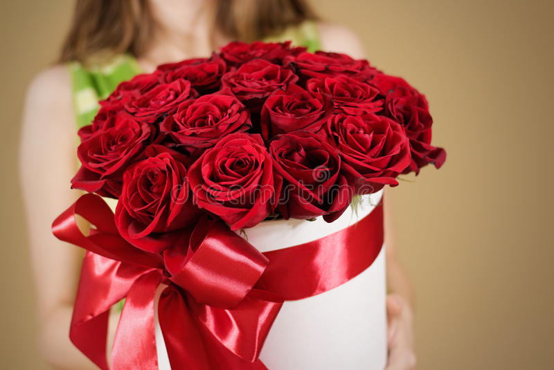 Девушка держа в букете подарка руки богатом 21 красной розы Composit стоковое изображение