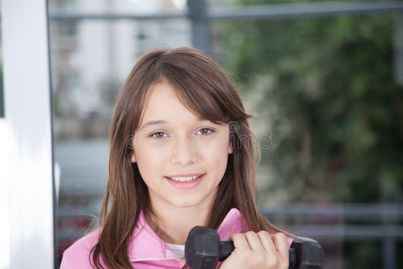 Девушка держа гантель стоковое изображение rf