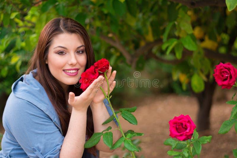 Девушка держа красные розы стоковое фото