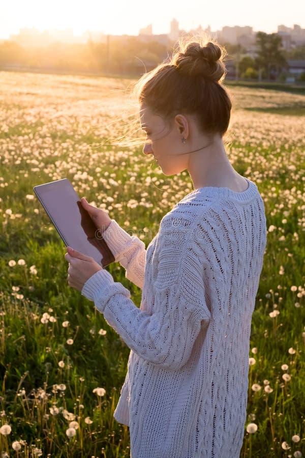 Девушка держа планшет в свете захода солнца стоковая фотография