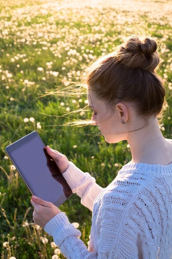 Девушка держа планшет в свете захода солнца стоковое фото