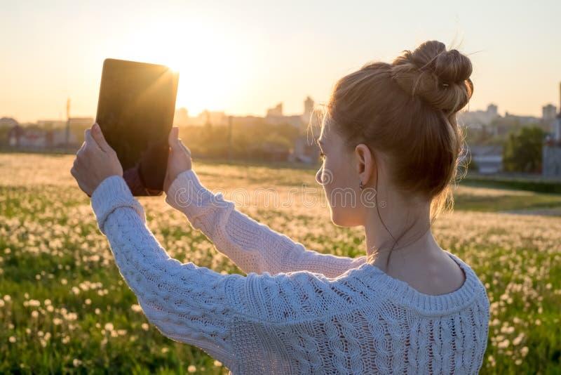 Девушка держа планшет в свете захода солнца стоковое изображение