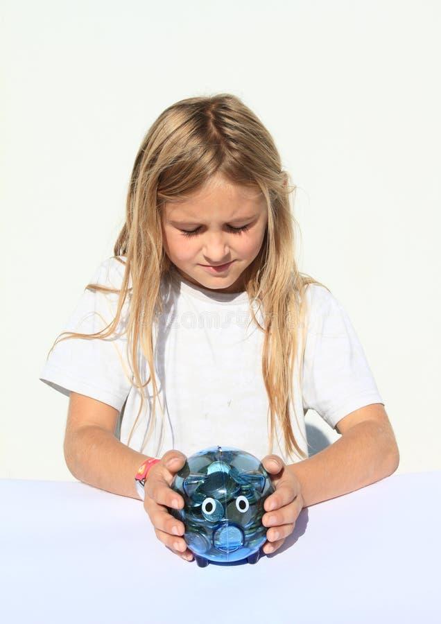 Девушка держа свинью сбережений полный денег стоковое фото