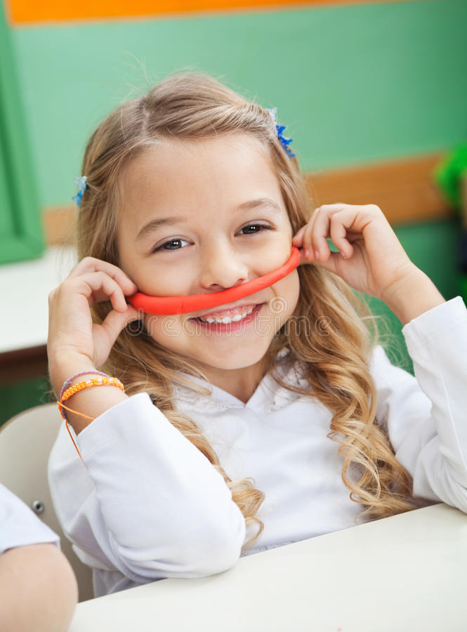 Девушка держа усик сделанный из глины в Preschool стоковые фотографии rf