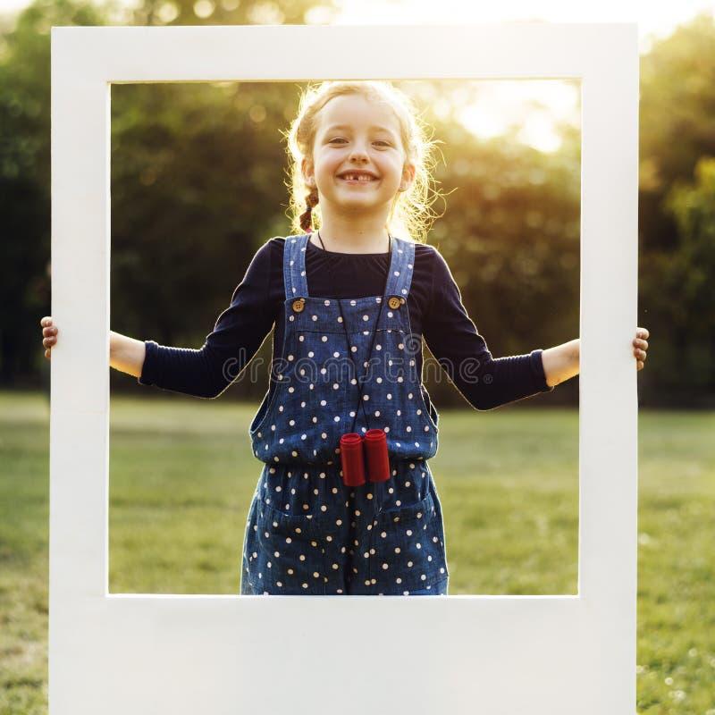 Девушка держит рамку в парке стоковое изображение rf