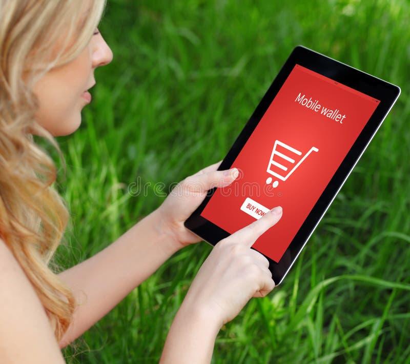 Девушка держит таблетку и делает онлайн покупки стоковые фото