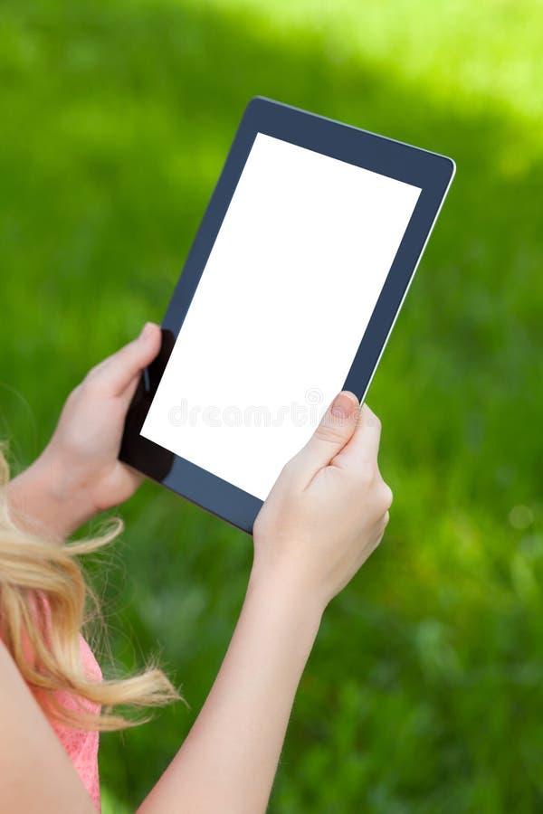 Девушка держит таблетку на предпосылке зеленой травы стоковые изображения
