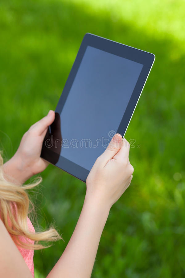 Девушка держит таблетку на предпосылке зеленой травы стоковое фото