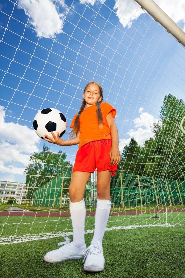 Девушка держит футбол, стоит перед работой по дереву стоковое фото