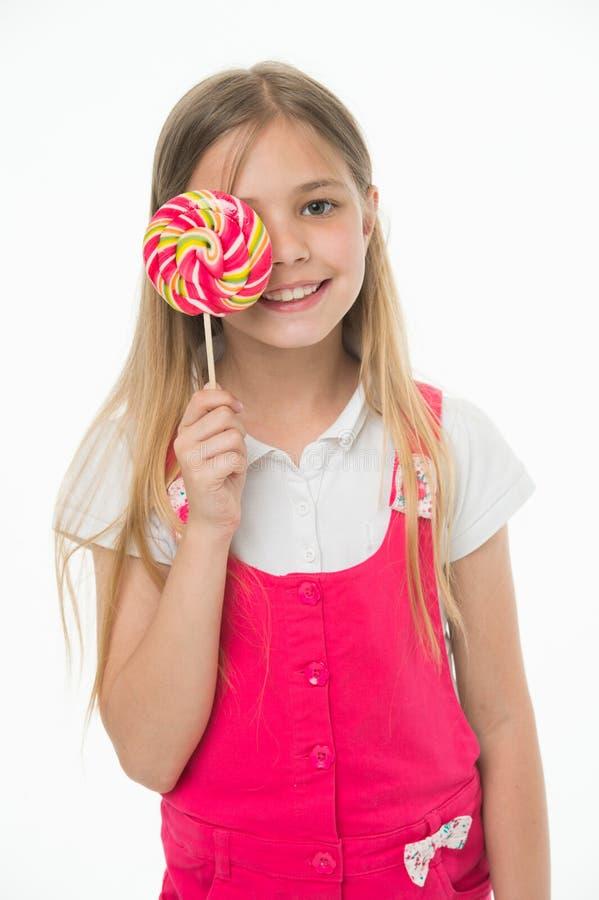 Девушка есть большую конфету на ручке или леденце на палочке Девушка на усмехаясь стороне держит гигантский красочный леденец на  стоковое изображение