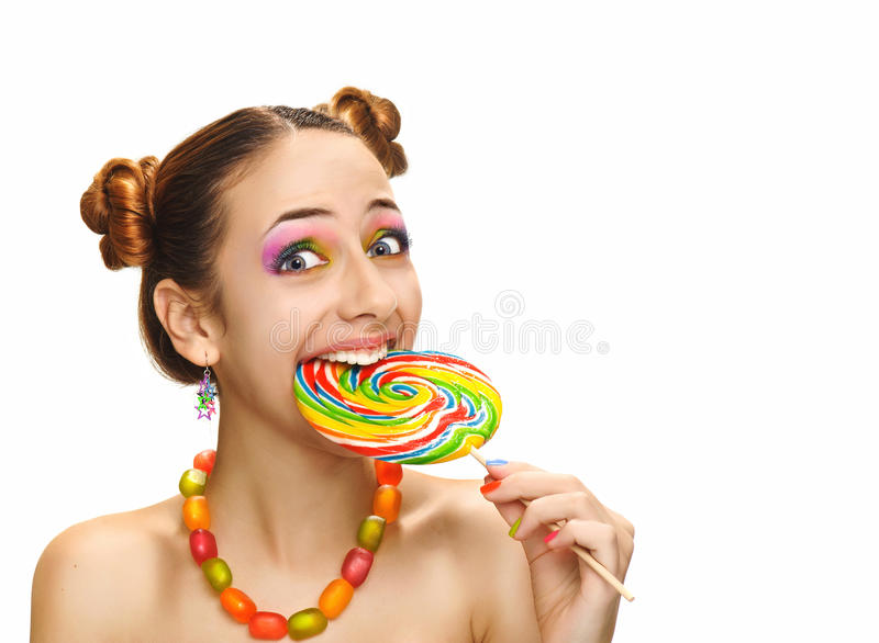 Девушка есть красочный леденец на палочке стоковые изображения