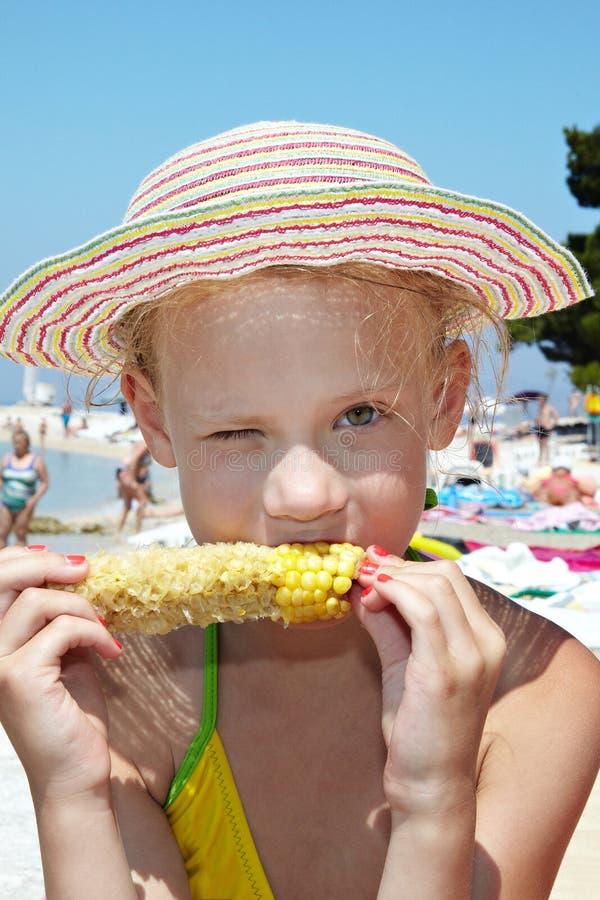 Девушка есть мозоль на пляже стоковые изображения rf
