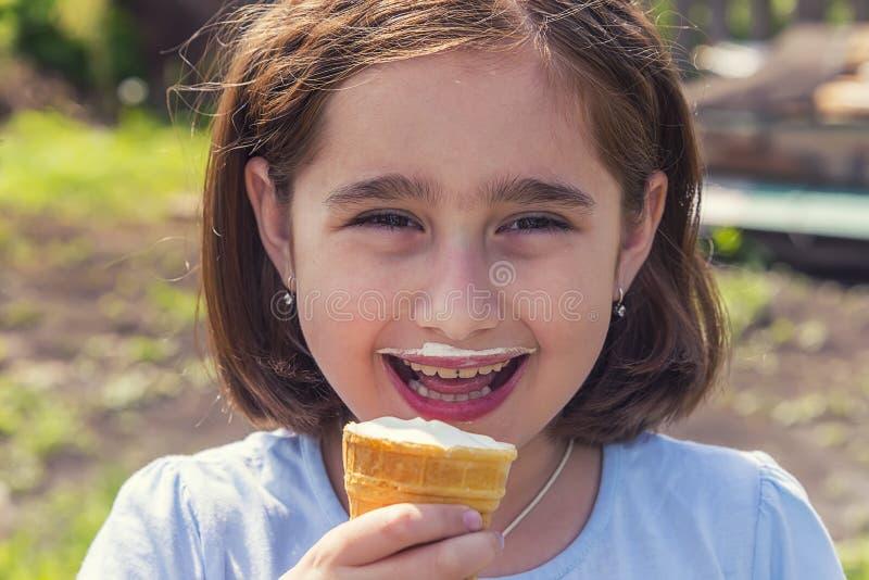 Девушка есть мороженое в чашке waffle стоковые фото