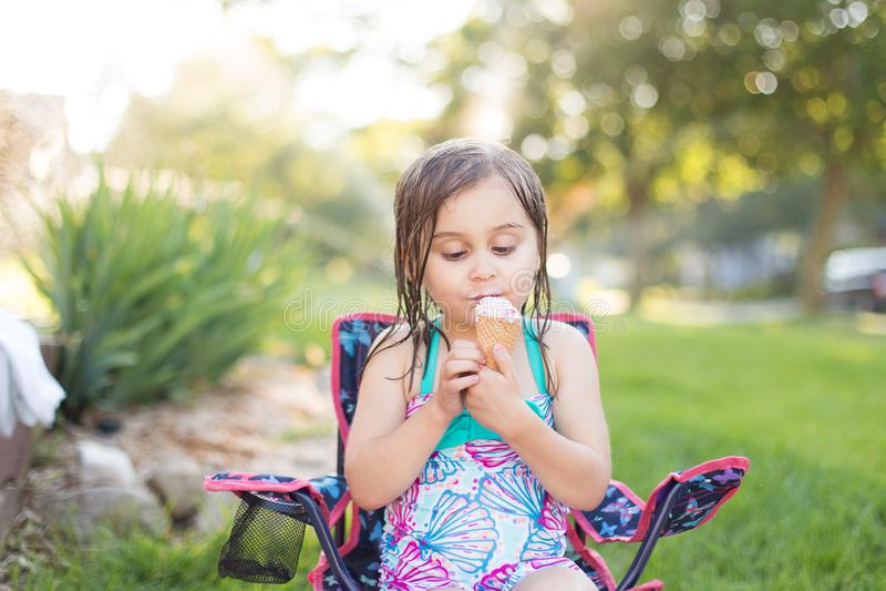 Девушка есть мороженое снаружи стоковые изображения rf