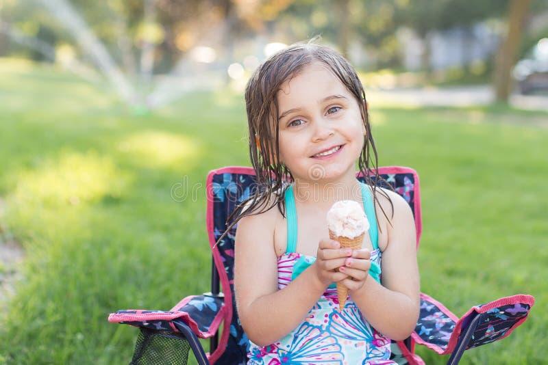 Девушка есть мороженое снаружи стоковое изображение