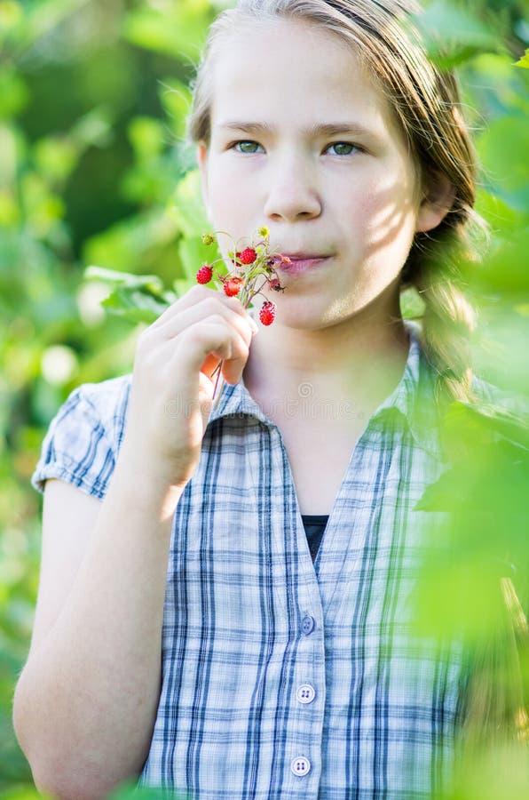 Девушка есть одичалые клубники стоковое изображение rf