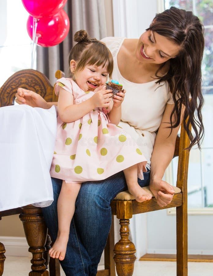 Девушка есть пирожное пока сидящ на подоле матери стоковые изображения