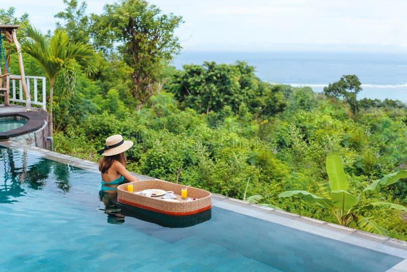 Девушка есть плавая завтрак в роскошном пейзажном бассейне стоковое изображение rf