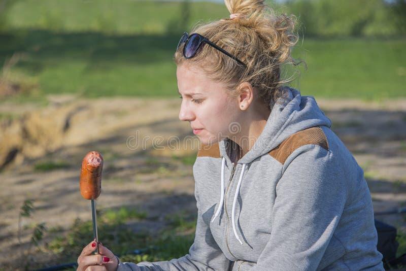 Девушка есть сосиску от гриля стоковые фото