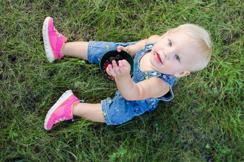Девушка ест ежевику стоковое изображение rf