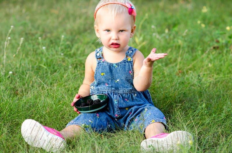 Девушка ест ежевику стоковое фото