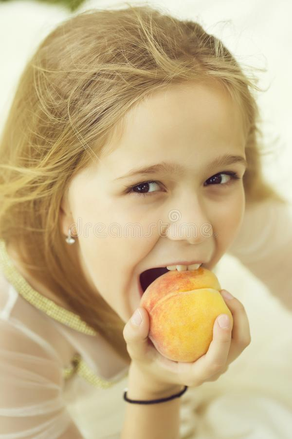 Девушка ест персик стоковые изображения