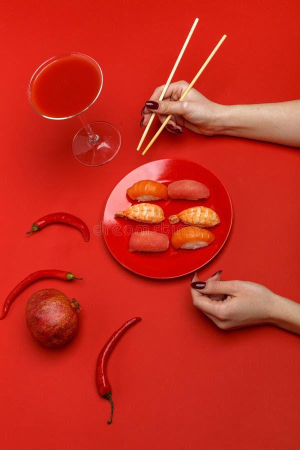 Девушка ест суши на красной плите Творческая концепция сервировки стола ресторана стоковое фото