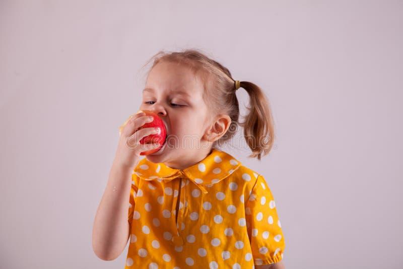 Девушка ест яблоко изолированное на белизне стоковые изображения rf