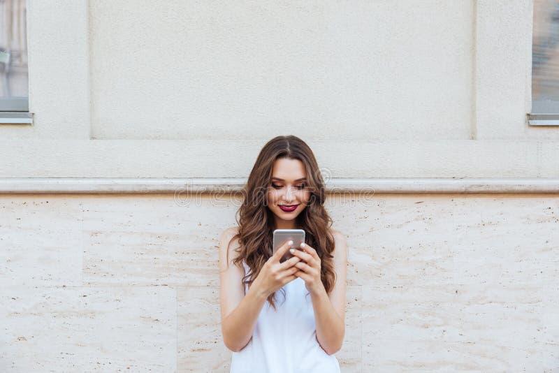 Девушка детенышей усмехаясь красивая используя ее телефон outdoors стоковое фото
