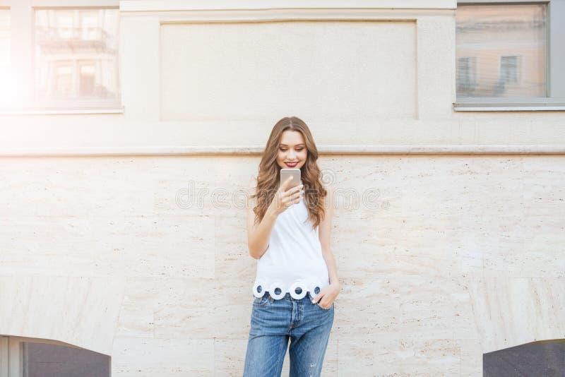 Девушка детенышей усмехаясь красивая используя ее телефон outdoors стоковые фото
