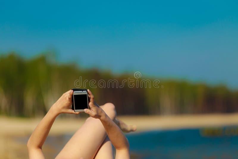 Девушка летних каникулов с телефоном загорая на пляже стоковые изображения rf