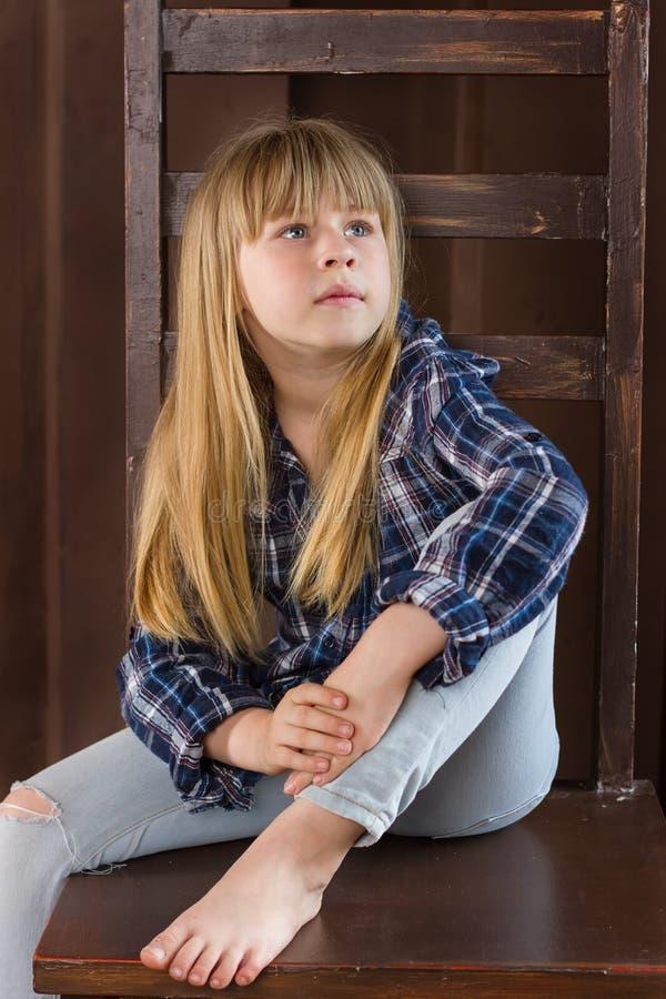 Девушка 6 лет старого усаживания на высоком стуле стоковое изображение rf