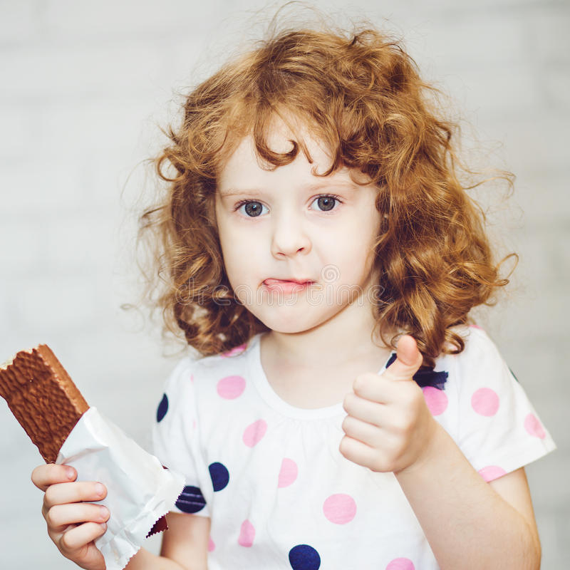 Девушка жадно держа шоколад на светлой предпосылке стоковое изображение