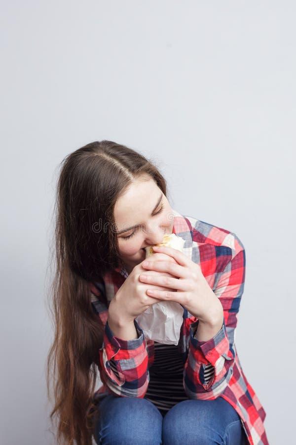 Девушка жадно ест крен стоковое фото rf