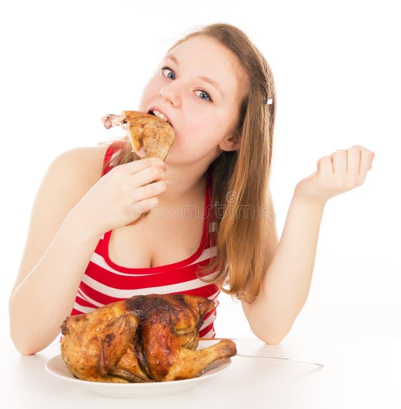 Девушка жадно поглощая часть цыпленка стоковые изображения