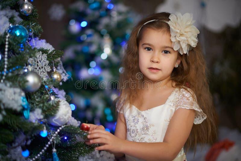 Девушка ждет настоящие моменты на рождественской елке стоковая фотография