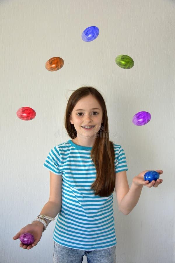 Девушка жонглируя пасхальными яйцами стоковое изображение rf
