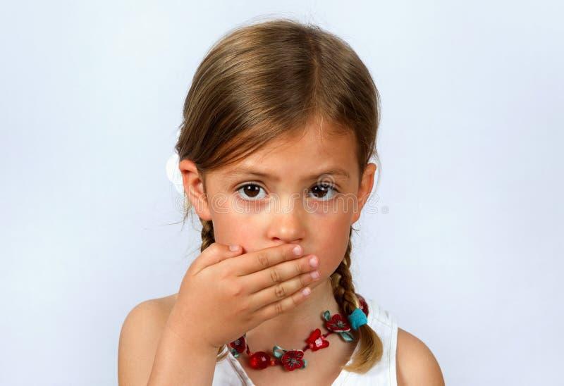 девушка заволакивания ее рот стоковое изображение