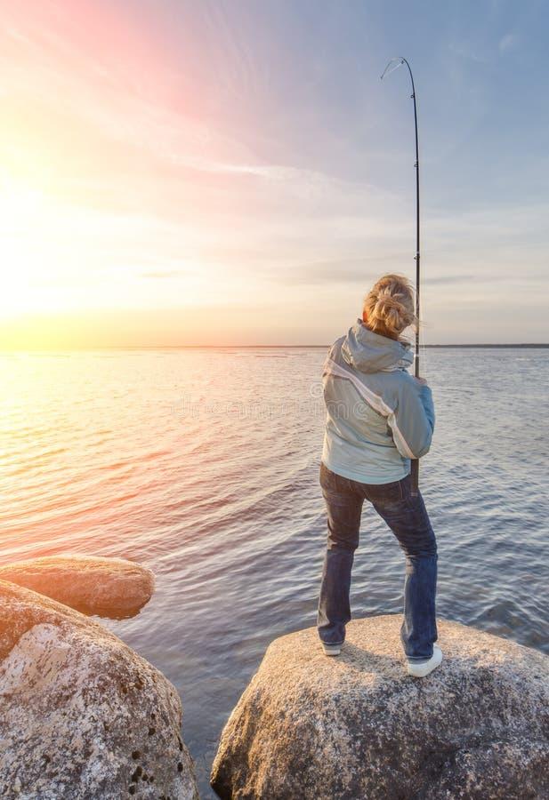 Девушка закрепляя рыбу на береге озера стоковые фотографии rf