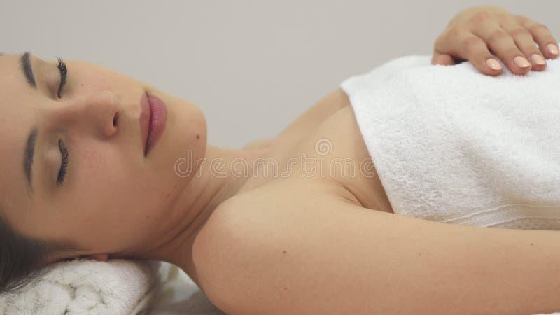 Девушка закрывает ее глаза на таблице массажа стоковые изображения rf