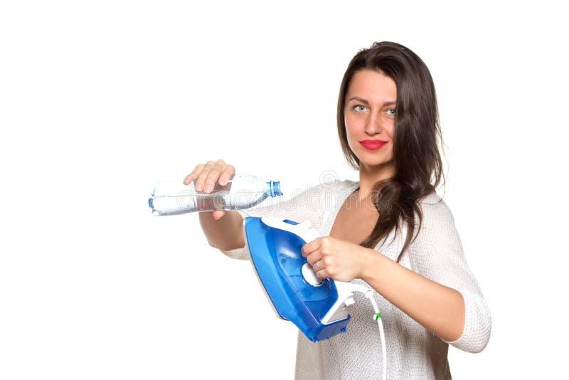 Девушка заполняет утюг внутри с водой стоковые фото