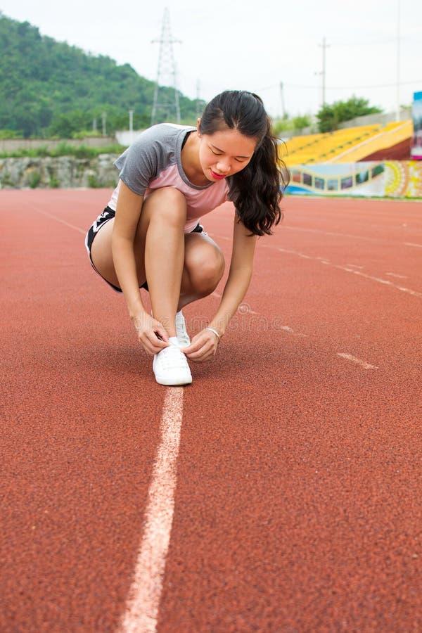 Девушка затягивая шнурки на jogging следе стоковые изображения rf