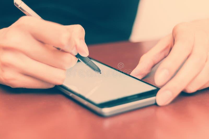 Девушка за столом со смартфоном и грифелем стоковые фото