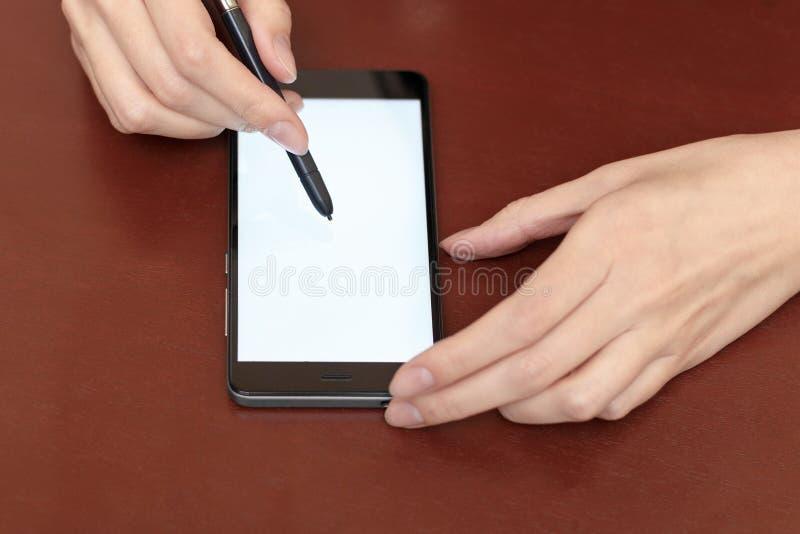 Девушка за столом со смартфоном и грифелем стоковые фотографии rf