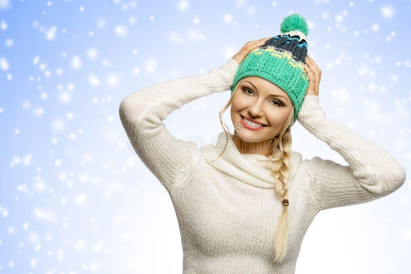 Девушка зимы представляя и усмехаясь стоковое фото