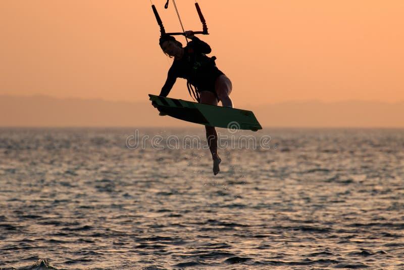 Девушка змея занимаясь серфингом в купальнике со змеем в небе на борту в движении фокуса фристайла моря скача Рекреационная деяте стоковое фото