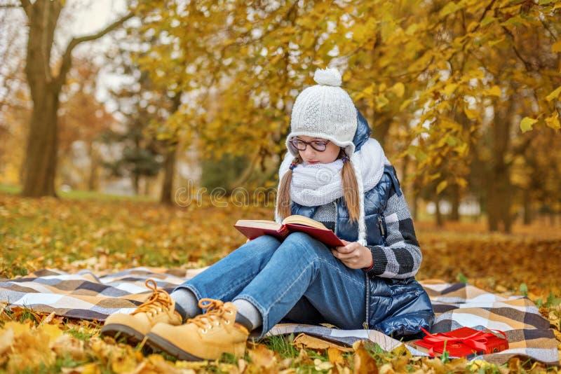 Девушка зрачка подростка в учебнике исследований стекел в парке сидит на шотландке в уютных белых шарфе и шляпе стоковые изображения rf
